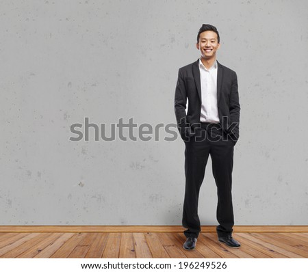 handsome young asian man smiling wearing a suit - stock photo