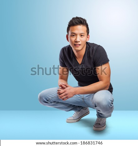 handsome young asian man squatting in a blue room - stock photo