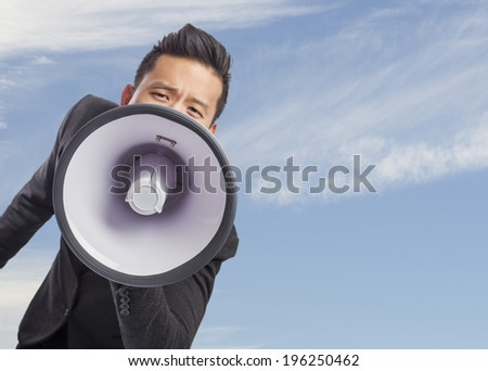 handsome young asian man with a megaphone - stock photo