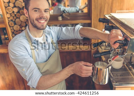 Handsome young barista is making coffee using a modern coffee machine in the urban cafe, looking at camera and smiling