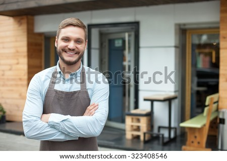 Handsome young barista is standing near his cafe outdoors. He is looking forward and smiling. The man crossed his arms with confidence - stock photo