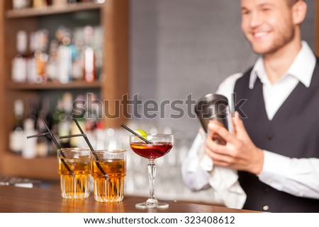 Handsome young barman is making cocktails in bar. He is standing and holding shaker. The man is smiling. Focus on glasses of beverage - stock photo