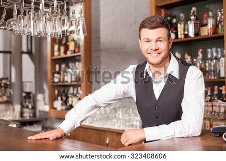 Handsome young barman is waiting for customer in bar. He is standing at counter and smiling. The man is looking at camera happily - stock photo