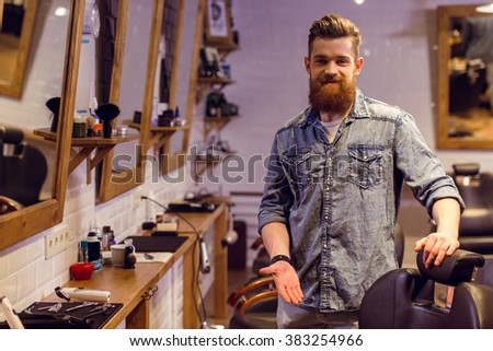 Handsome young bearded barber pointing on a chair, looking at camera and smiling while standing in the barber shop - stock photo