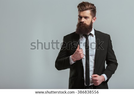 Handsome young bearded businessman in classic suit is adjusting his jacket and looking away, on a gray background - stock photo