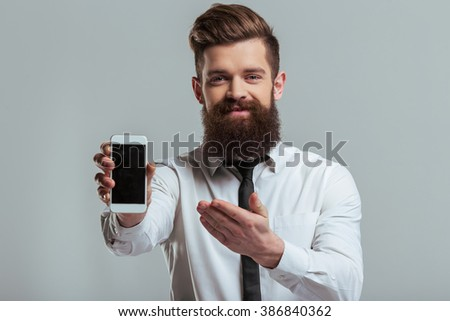 Handsome young bearded businessman in classic white shirt is showing a mobile phone and smiling, on a gray background - stock photo
