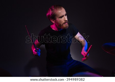 Handsome young bearded man drummer sitting and playing drums with drumsticks over dark background - stock photo