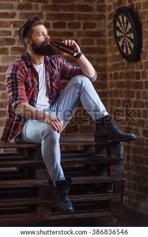 Handsome young bearded man in casual clothes is drinking beer and looking away, sitting against brick wall - stock photo
