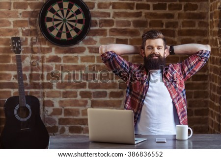 Handsome young bearded man in casual clothes is resting and smiling after working with a laptop - stock photo