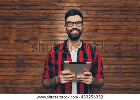 Handsome young bearded man in glasses holding tablet - stock photo