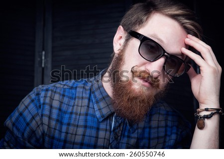 Handsome young bearded man in sunglasses looking away from camera - stock photo