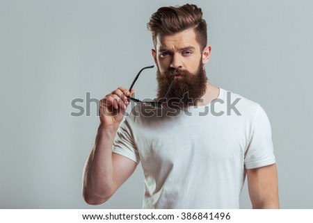 Handsome young bearded man is holding sunglasses and looking at camera while standing against gray background - stock photo