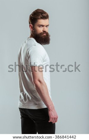 Handsome young bearded man is looking at camera while standing turned against gray background - stock photo