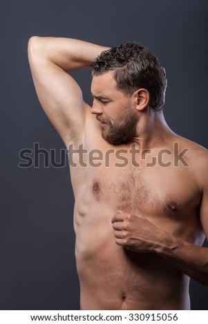 Handsome young bearded man is standing and posing. He is raising his arm behind head. The man is looking at his forearm seriously. Isolated on grey background - stock photo