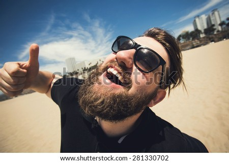 Handsome young bearded man making fun, laughing and posing with thumbs up on Santa Monica beach while travel in Los Angeles, California - stock photo