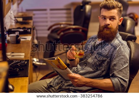 Handsome young bearded man reading a magazine and holding a glass of beverage while sitting on a chair at the barber shop - stock photo