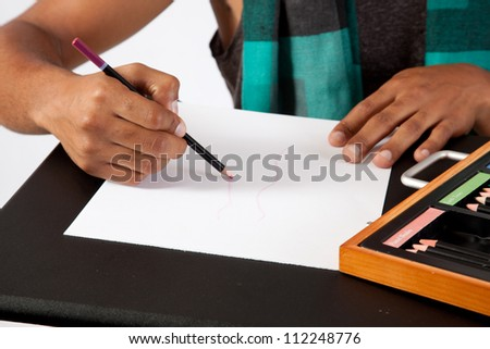handsome young black man drawing with colored pastels as he designs clothing