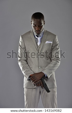 Handsome young black man in a business suit stands with his firearm down in front of him. - stock photo