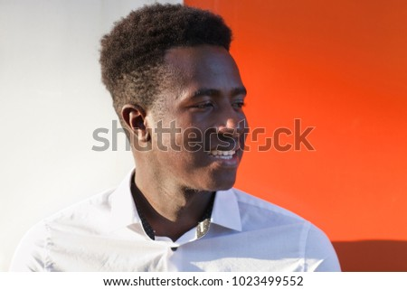 Handsome young black man looking to the side and smiling in front of orange and white divided background