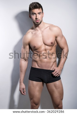 handsome young bodybuilder with toned body posing shirtless - stock photo