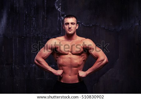 Handsome young bodybuilder with toned muscular body posing shirtless in dark studio