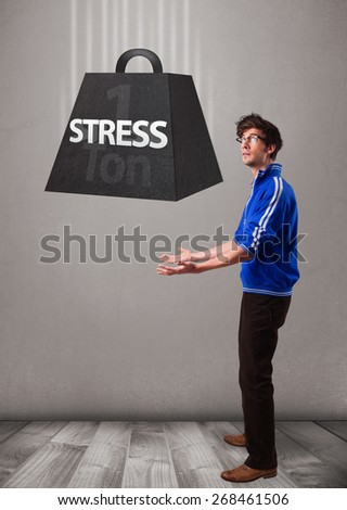 Handsome young boy holding one ton of stress weight - stock photo