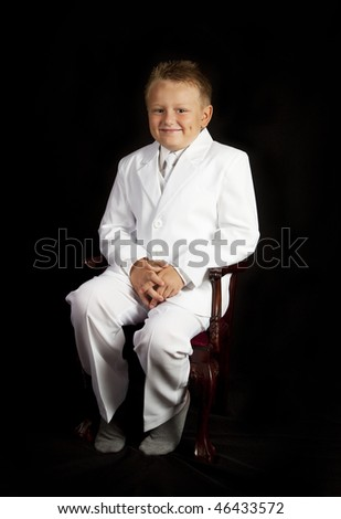 Handsome Young Boy in a White Suit sitting in chair