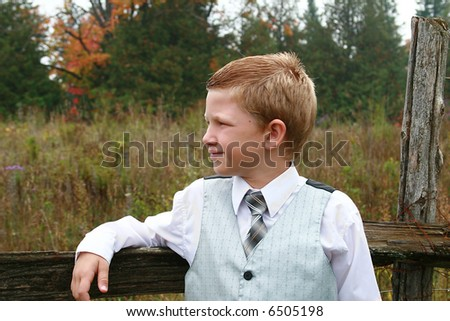 Handsome young boy leaning on a fence post.