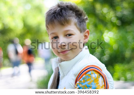 Handsome young boy portrait. Smiling kid boy looking at camera on the street on green nature background. Little boy, child outdoors in summer or spring. - stock photo