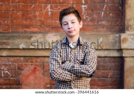 Handsome young boy portrait. Stylish smiling kid boy on the street looking at camera on the red brick wall urban city background. Teenage boy, child outdoors. - stock photo