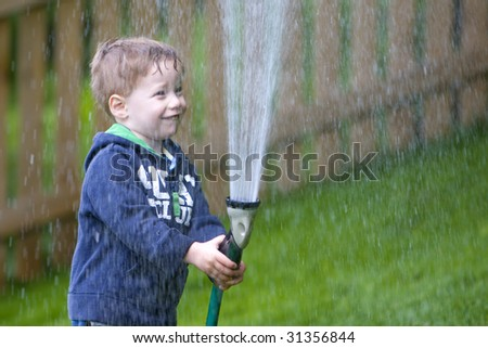 Handsome young boy watering garden with rubber hosepipe - stock photo