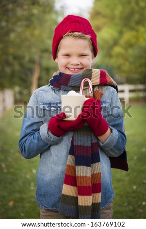 Handsome Young Boy Wearing Holiday Clothing Holding Hot Cocoa with Marshmallows and Candy Cane Outside. - stock photo