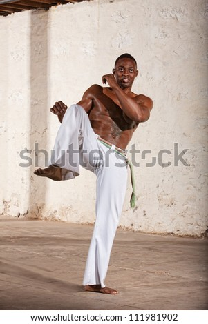 Handsome young Brazilian man doing a Capoeria knee kick - stock photo