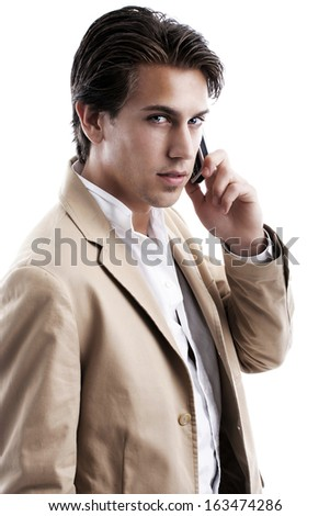 Handsome young business man chatting on his mobile phone staring at the camera with a thoughtful expression as he listens to the conversation