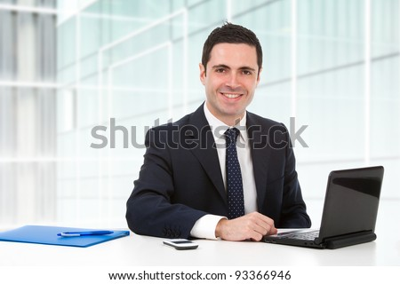 Handsome young business man in blue suit in office with laptop. - stock photo