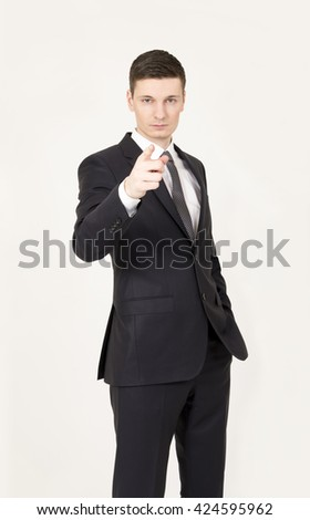 Handsome young business man points finger at you on the gray background. - stock photo