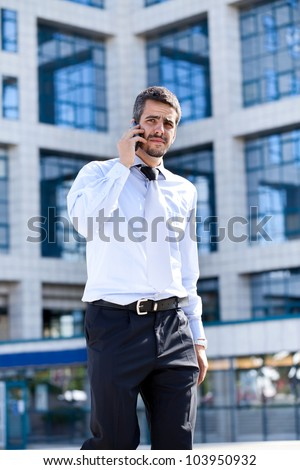 Handsome young business man speaking on the phone , outdoor