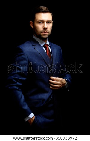 Handsome young business man standing on black