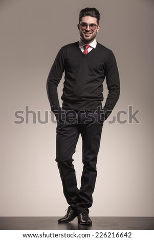 Handsome young business man standing on grey studio background holding his hands in pocket.  - stock photo