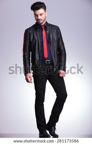 Handsome young business man standing on grey studio background looking down, full body picture. - stock photo