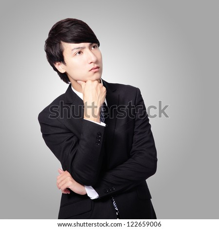 Handsome young business man think looking up to empty copy space, businessman hold hand behind head, wear elegant suit and tie, isolated gray background, asian male model