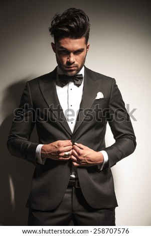 Handsome young business man unbuttoning his jacket while looking at the camera. - stock photo