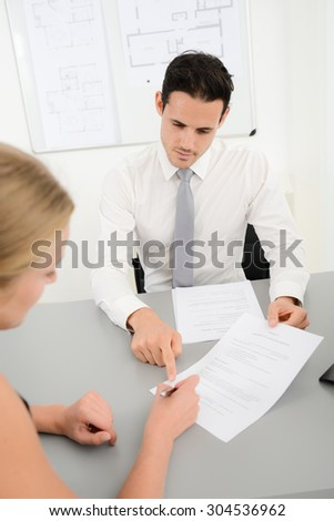 handsome young business man with customer in office signing agreement sales contract