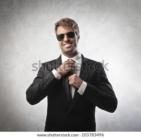 Handsome young businessman adjusting his tie - stock photo