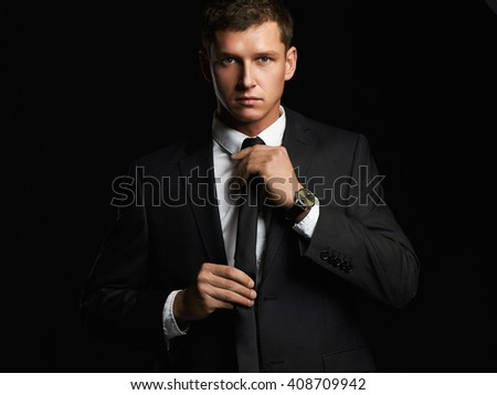 Handsome young businessman adjusting his tie while standing against black background. young man in suit - stock photo
