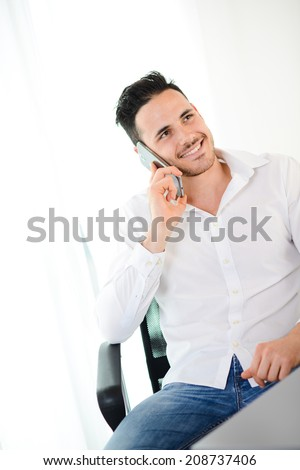 handsome young businessman at office with casual friday wear clothes having a telephone conversation - stock photo