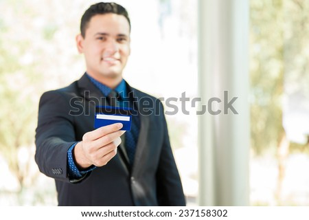 Handsome young businessman blurred in the background and holding a credit card in his hand - stock photo