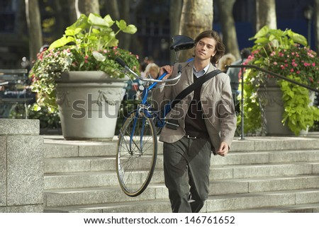 Handsome young businessman carrying bicycle down steps in park - stock photo