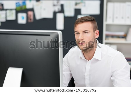 Handsome young businessman concentrating on his work as he reads information on a large desktop monitor - stock photo