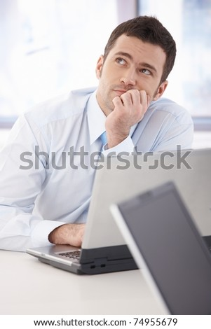 Handsome young businessman daydreaming at desk in office.? - stock photo